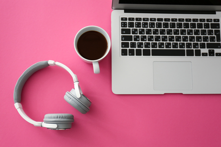 Headphones with laptop and cup of coffee on color table