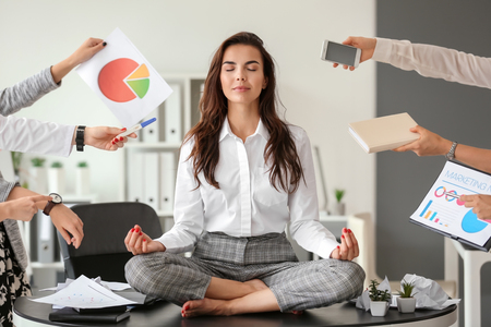 Businesswoman with a lot of work to do meditating in office Stock Photo
