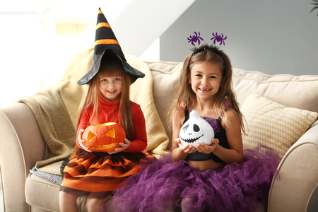 Cute little girls in Halloween costumes at home