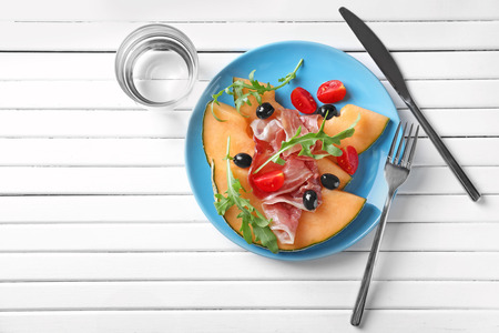 Plate with delicious melon and prosciutto on white wooden table, top view