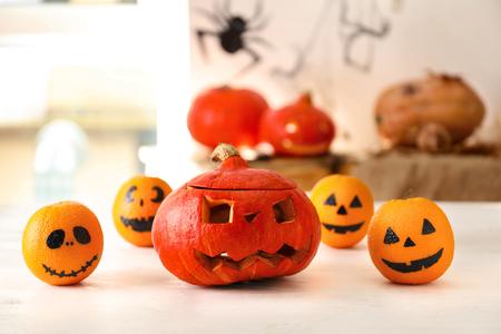 Creative oranges with Halloween pumpkin on light wooden table
