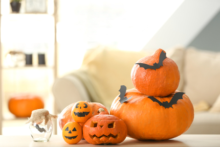 Halloween pumpkins with creative oranges and paper bats on table