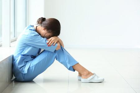 Tired female nurse sitting on floor in hospital Фото со стока - 115148741