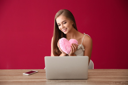 Young woman with laptop having online dating on color background 免版税图像