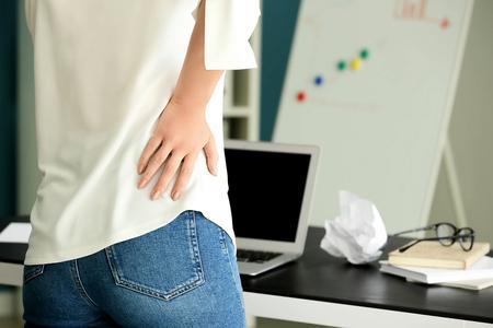 Junge Frau mit Rückenschmerzen im Büro Standard-Bild