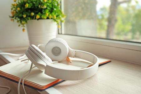Open notebook and headphones on windowsill