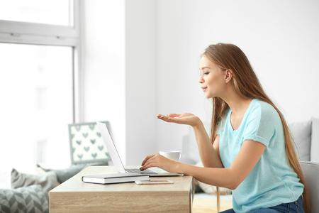 Junge Frau beim Online-Dating zu Hause