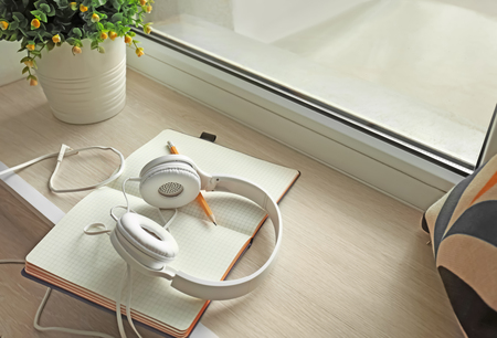 Open notebook and headphones on windowsill