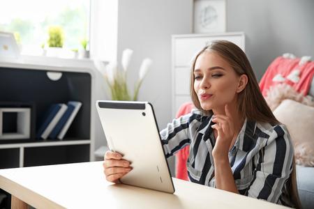 自宅でオンラインデートを持つタブレットコンピュータを持つ若い女性 写真素材