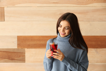 Woman with glass of delicious mulled wine on wooden background