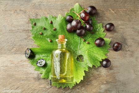 Composition with grape seed oil on wooden background