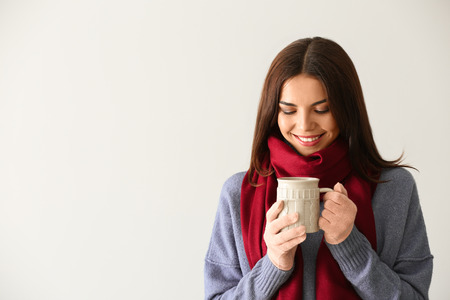 Woman with mug of delicious mulled wine on light background