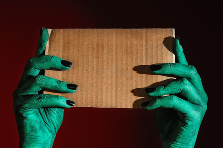 Monster holding blank card on dark background Archivio Fotografico