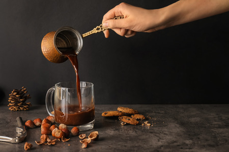 Woman pouring hot chocolate from cezve into glass cup on dark table