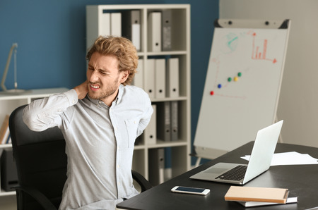 Businessman suffering from neck pain in office Stock Photo