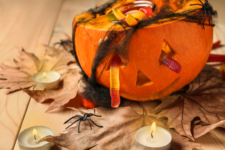 Pumpkin with jelly candies prepared for Halloween party on wooden table Stock Photo