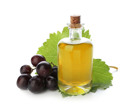 Bottle with grape seed oil on white background