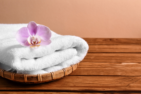 Wicker tray with clean soft towel and flower on wooden table Archivio Fotografico