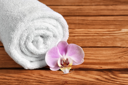Rolled clean soft towel with flower on wooden table