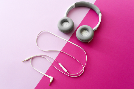 Modern headphones and earphones on color background