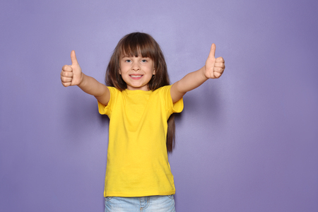 Little girl in t-shirt showing thumb-up gesture on color background