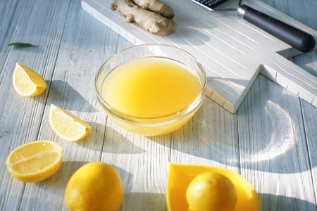 Glass bowl with freshly squeezed lemon juice on color wooden table