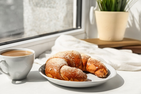Plate with tasty fresh crescent roll and cup of cocoa drink on windowsill