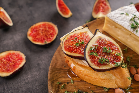 Tasty sandwich with ripe fig and brie cheese on wooden plate, closeup