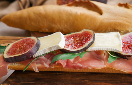 Tasty sandwich with ripe fig, prosciutto and brie cheese on wooden board, closeup