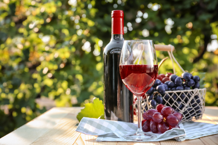 Glass and bottle of red wine with fresh grapes on wooden table in vineyard Banco de Imagens