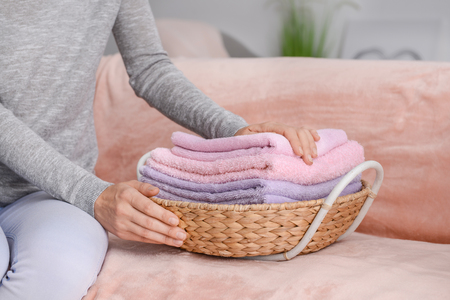 Woman folding clean soft towels into wicker basket on sofa at home