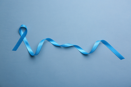 Blue ribbon on color background. Cancer concept