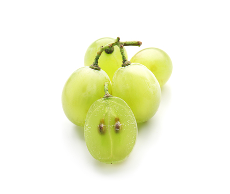 Cut and whole ripe juicy grapes with seeds on white background