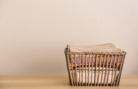 Laundry basket with clean towels on table near white wall