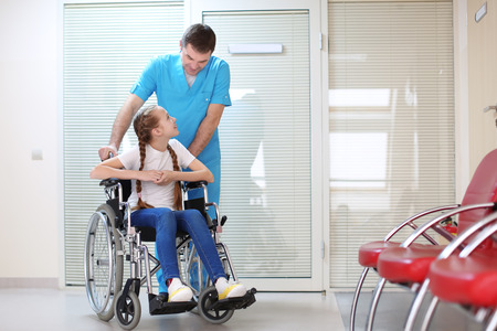 Male doctor taking care of little girl in wheelchair indoors