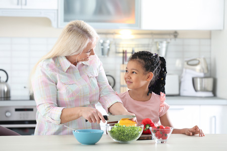 Female mature nanny teaching little African-American girl to cut vegetables in kitchen