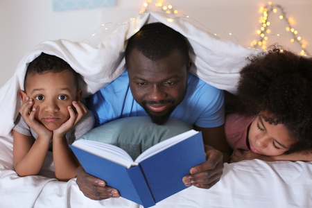 African American man reading bedtime story to his children in bed