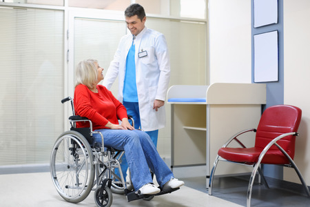 Male doctor taking care of mature woman in wheelchair indoors Imagens