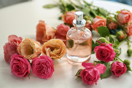 Bottle of perfume with beautiful flowers on white table