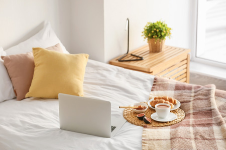 Wicker mat with delicious breakfast and laptop on bed Stock Photo