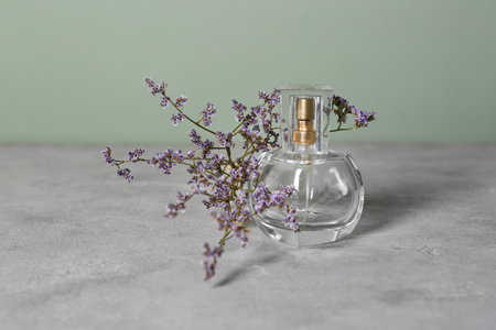 Transparent bottle of perfume with beautiful flowers on grey table