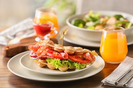 Assiette avec de délicieuses gaufres à bulles et verre de jus d'orange sur une table en bois