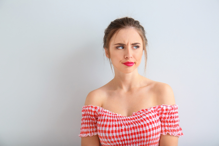 Displeased young woman on light background Stock Photo