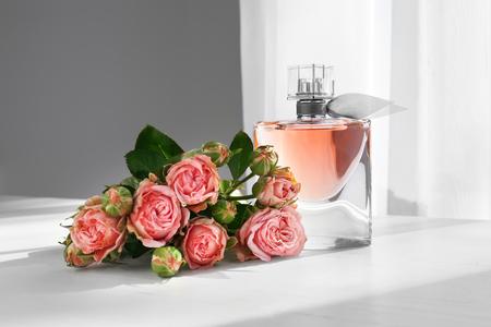 Transparente Parfümflasche mit schönen Blumen auf weißem Tisch