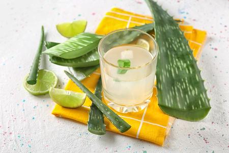 Glass of aloe vera juice on white table Stock Photo