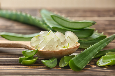 Spoon with aloe vera on wooden table