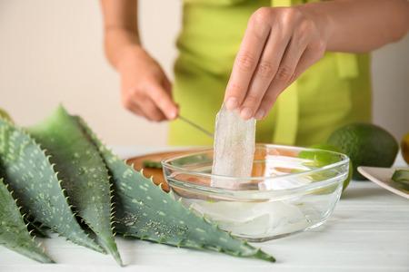 Woman making aloe vera gel at table