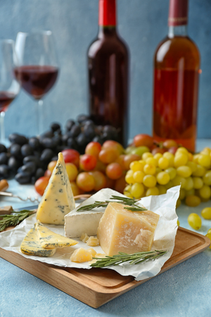 Different types of cheese with rosemary on wooden board