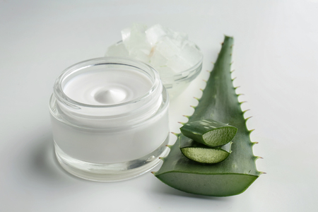 Jar with cream and aloe vera on white background