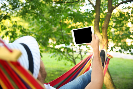 Handsome young man with tablet PC resting in hammock outdoors